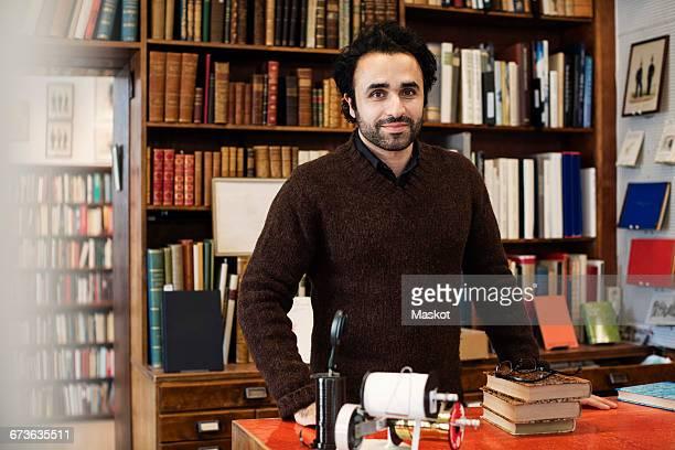 Portrait of smiling librarian standing against bookshelves