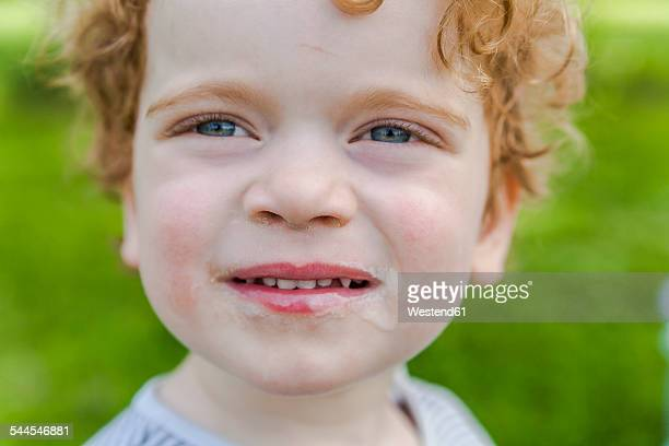 Portrait of smiling little boy covered with ice cream