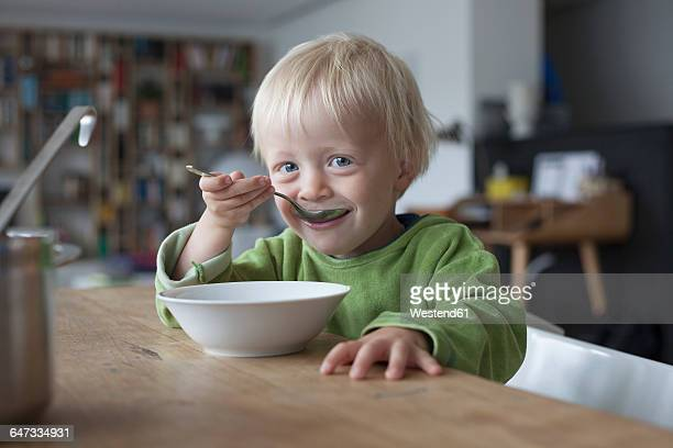 Portrait of smiling little boy eating soup at home