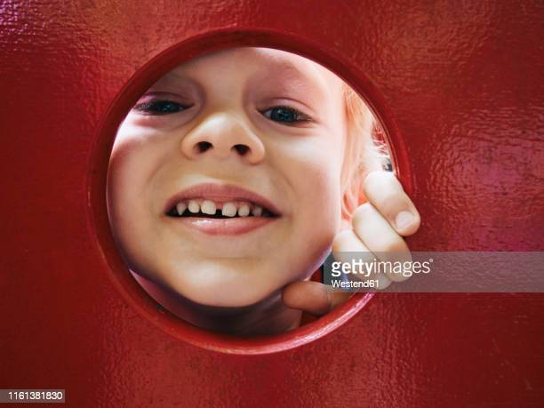 portrait of smiling little boy looking through hole on playground - peeping holes ストックフォトと画像