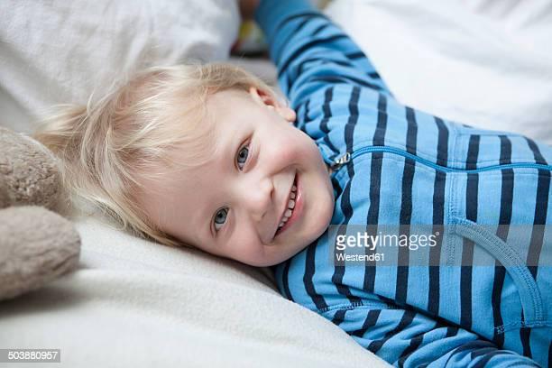 portrait of smiling little boy lying on blanket - menino loiro olhos azuis imagens e fotografias de stock