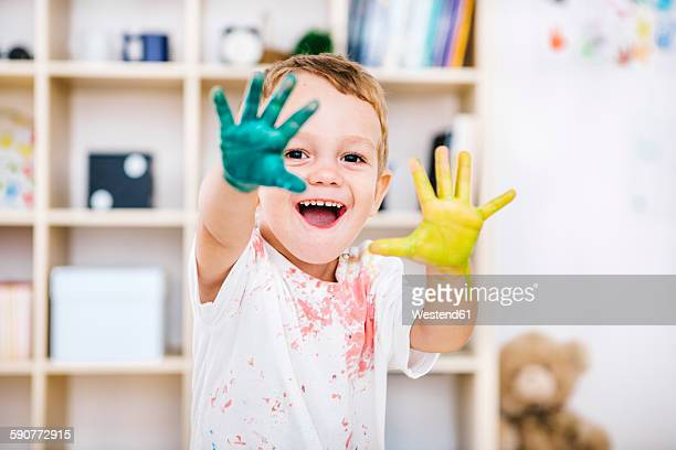 Portrait of smiling little boy showing his painted hands