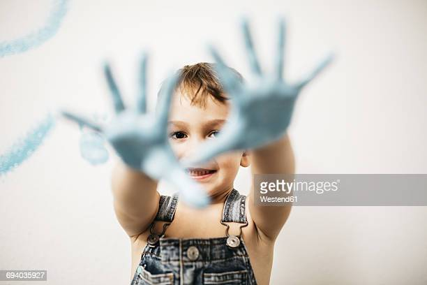 Portrait of smiling little boy showing his palms full of light blue colour