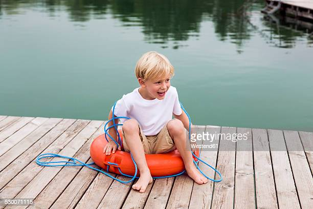 Portrait of smiling little boy sitting in a lifesaver on a jetty