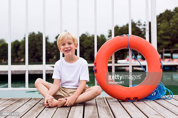 Portrait of smiling little boy sitting on a jetty besides a lifesaver