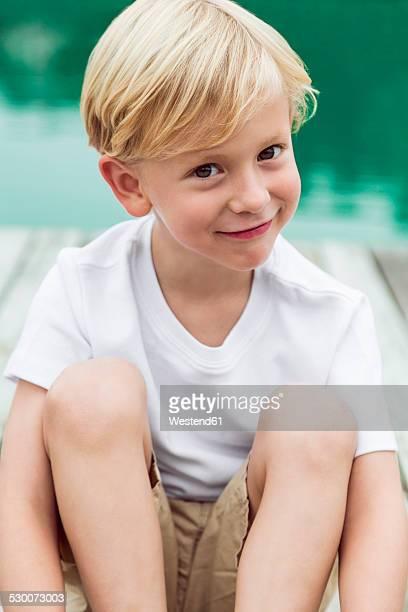 Portrait of smiling little boy sitting on a jetty