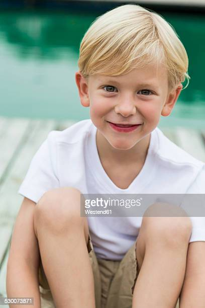 portrait of smiling little boy sitting on a jetty - only boys stock photos and pictures