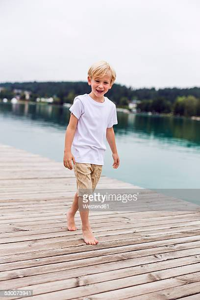 Portrait of smiling little boy walking on a jetty at a lake