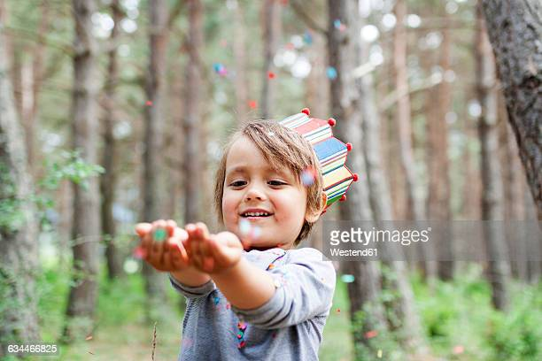 Portrait of smiling little boy wearing paper crown catching confetti