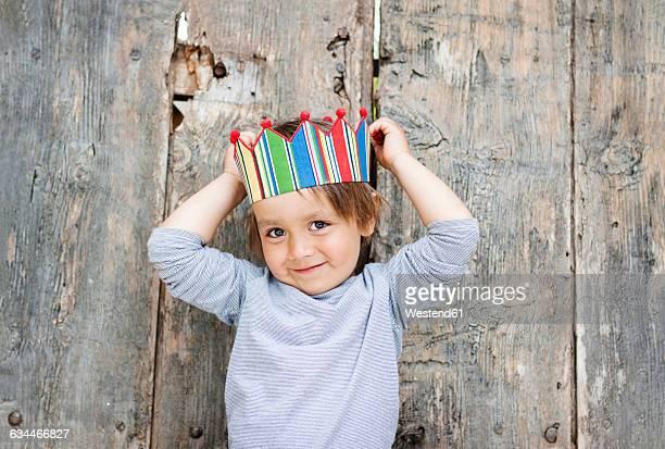 Portrait of smiling little boy wearing paper crown