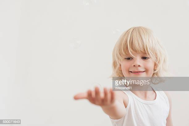 Portrait of smiling little boy with outstretched arm watching a soap bubble