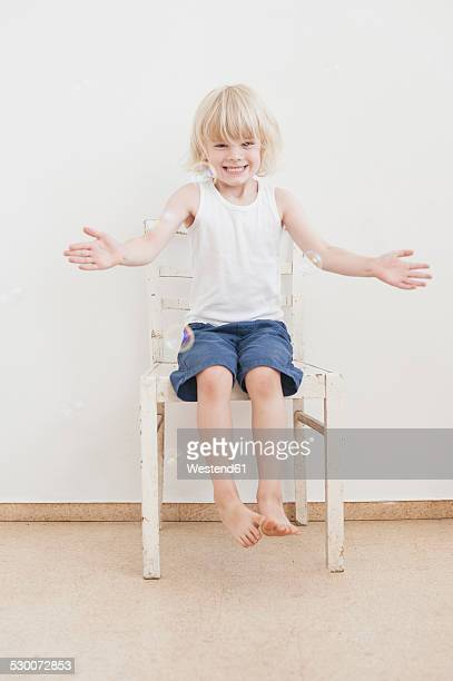 Portrait of smiling little boy with outstretched arms watching soap bubbles
