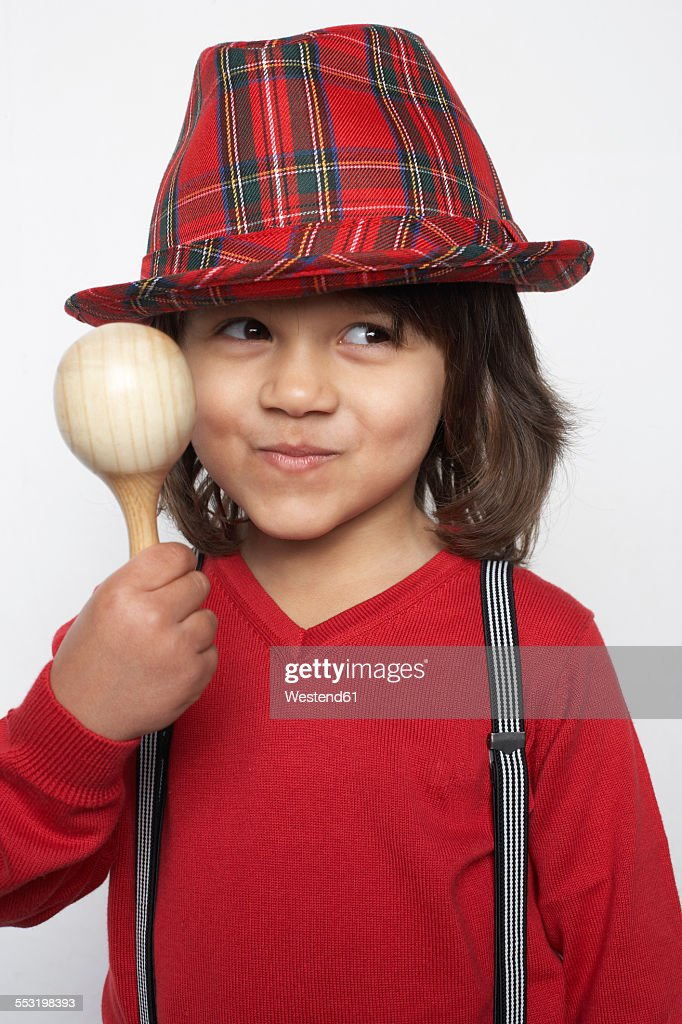 a9bbca36518 Portrait of smiling little boy with wooden rattle wearing hat and  suspenders   Stock Photo