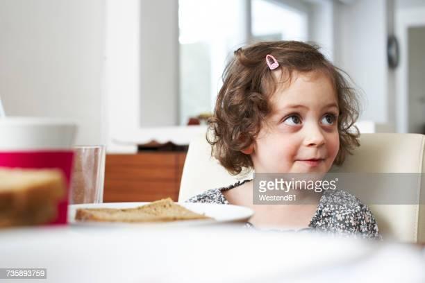 Portrait of smiling little girl at breakfast table