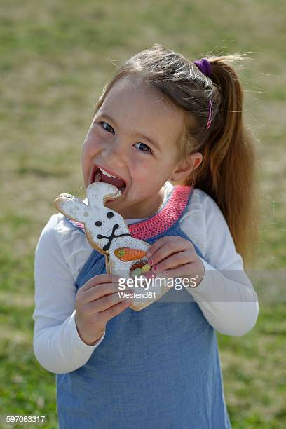 Portrait of smiling little girl biting off pastry formed like an Eastern Bunny
