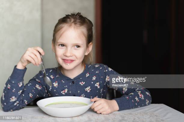portrait of smiling little girl eating oat meal - little russian girls stock photos and pictures