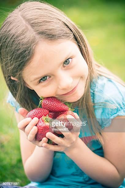 portrait of smiling little girl holding handful of strawberries - mädchen stock-fotos und bilder
