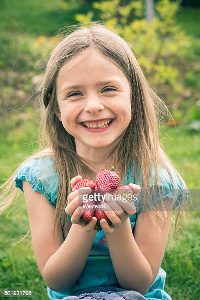 Portrait of smiling little girl holding handful of strawberries