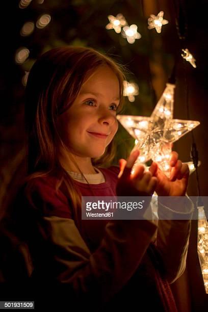 Portrait of smiling little girl holding lighted star of fairy lights