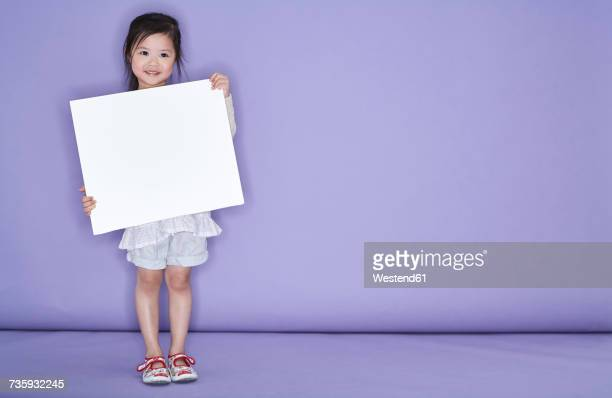 Portrait of smiling little girl holding white cardboard in front of purple background
