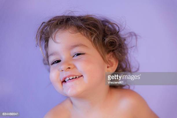 Portrait of smiling little girl in front of purple background