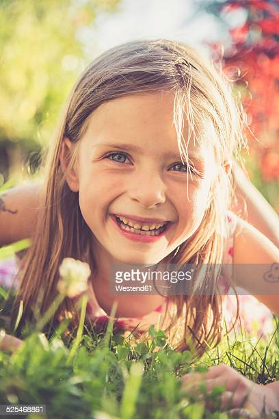 Portrait of smiling little girl lying on a meadow in the garden