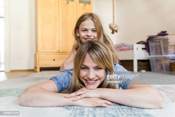 Portrait of smiling little girl lying on back of her mother on the floor