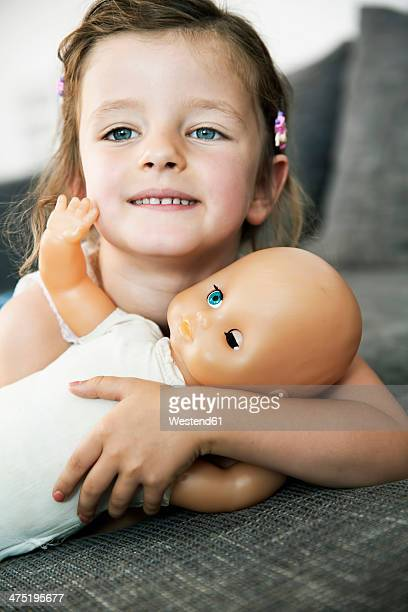 Portrait of smiling little girl lying on sofa with her doll, close-up