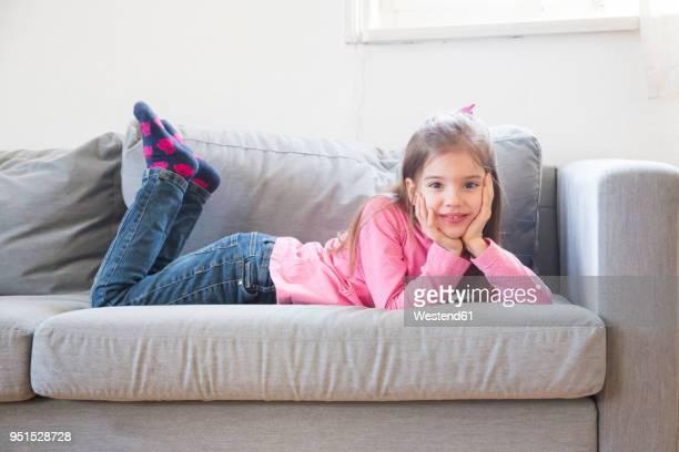 portrait of smiling little girl lying on the couch - op de buik liggen stockfoto's en -beelden