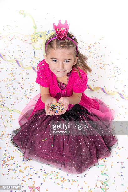 Portrait of smiling little girl masquerade as a princess holding confetti in her hands