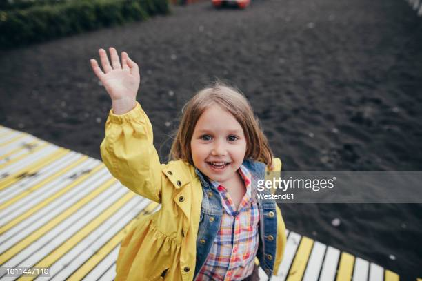 portrait of smiling little girl on boardwalk on black lava beach - waving stock pictures, royalty-free photos & images