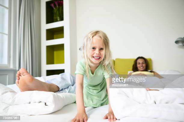 Portrait of smiling little girl on hotel bed with her parents