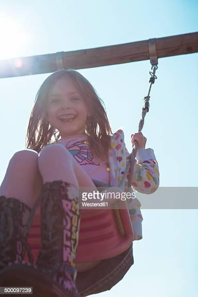 Portrait of smiling little girl on swing
