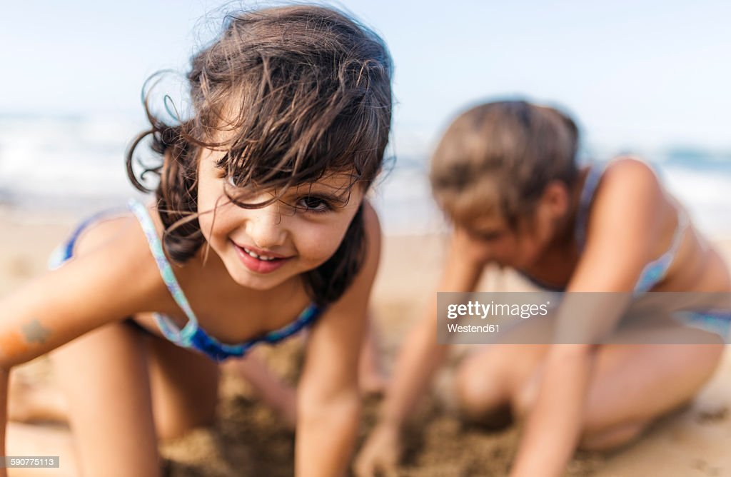 Portrait of smiling little girl playing on the beach : Stock Photo