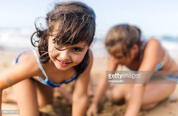 portrait of smiling little girl playing on the beach - little girls bent over stock photos and pictures
