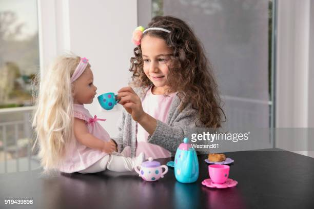 portrait of smiling little girl playing with doll and doll's china set - puppe stock-fotos und bilder