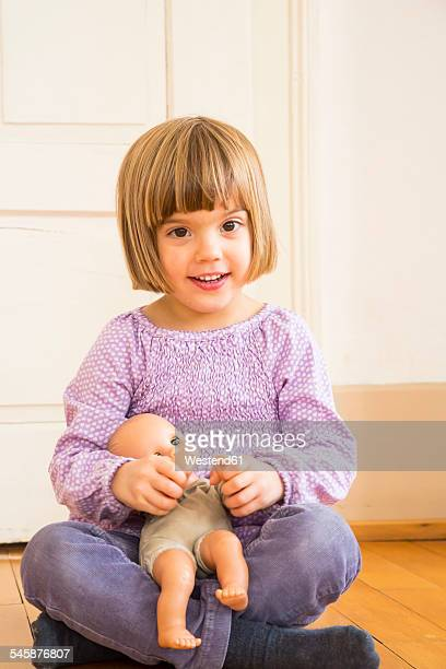 Portrait of smiling little girl playing with doll