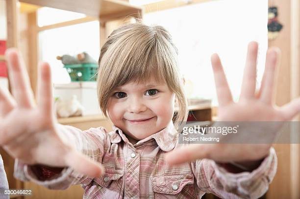 Portrait of smiling little girl showing her hands
