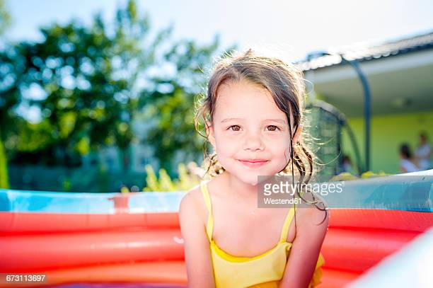 Portrait of smiling little girl sitting in paddling pool