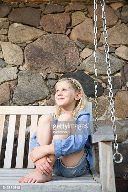 Portrait of smiling little girl sitting on a bench
