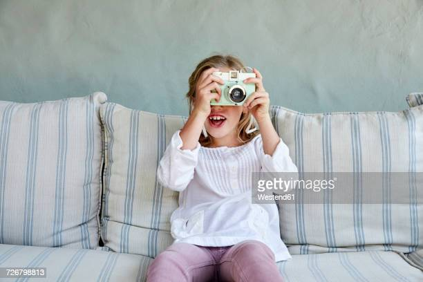 Portrait of smiling little girl sitting on couch taking picture with camera