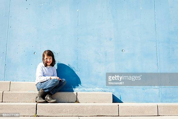 Portrait of smiling little girl sitting on steps in front of blue wall