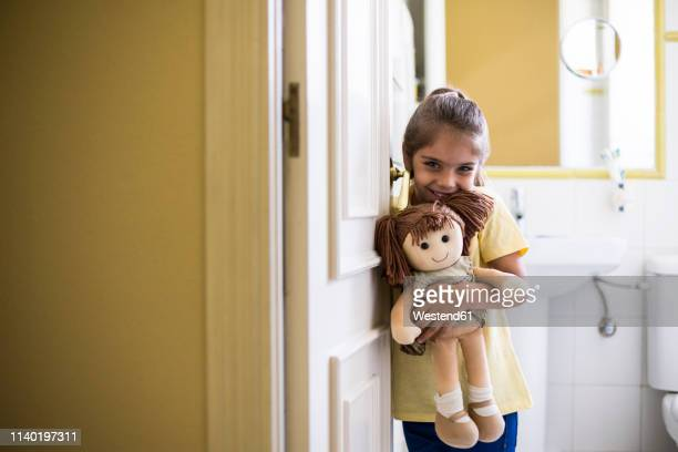 portrait of smiling little girl standing in doorframe at home holding a doll - puppe stock-fotos und bilder