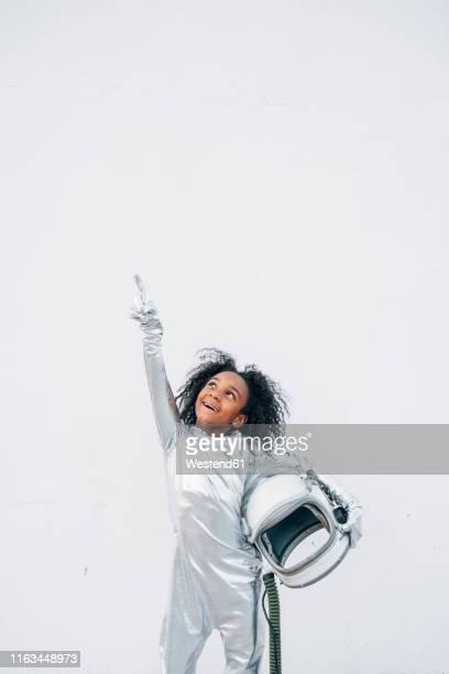 portrait of smiling little girl wearing space suit in front of white background looking up - astronaut stock pictures, royalty-free photos & images