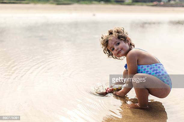portrait of smiling little girl wearing swim suit playing at seafront - little girls bent over stock photos and pictures