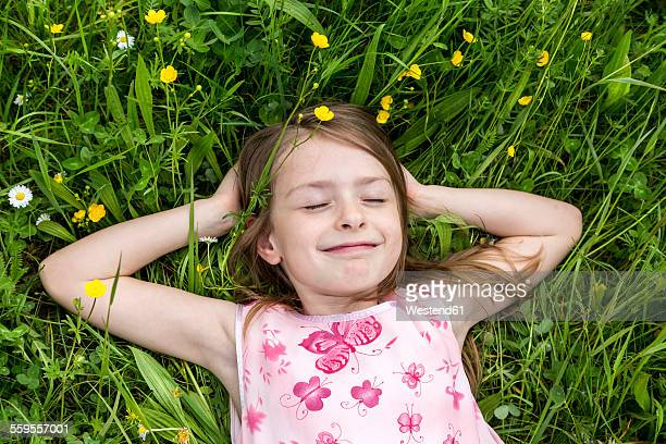 Portrait of smiling little girl with closed eyes lying on a flower meadow