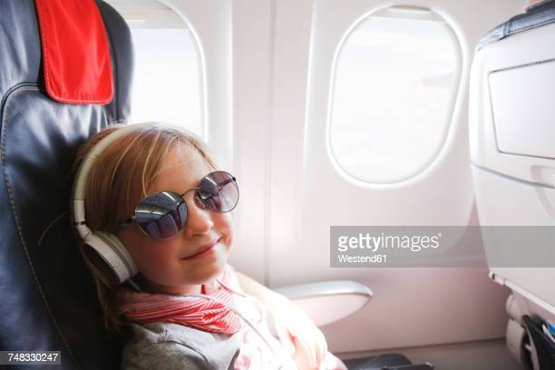 Portrait of smiling little girl with headphones sitting on an airplane
