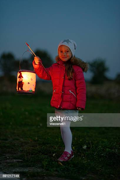 Portrait of smiling little girl with lighted paper lantern on St. Martins Day at twilight