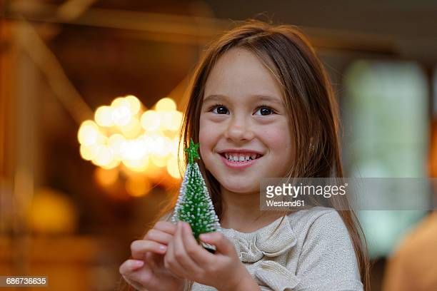 portrait of smiling little girl with miniature christmas tree - alleen één meisje stockfoto's en -beelden