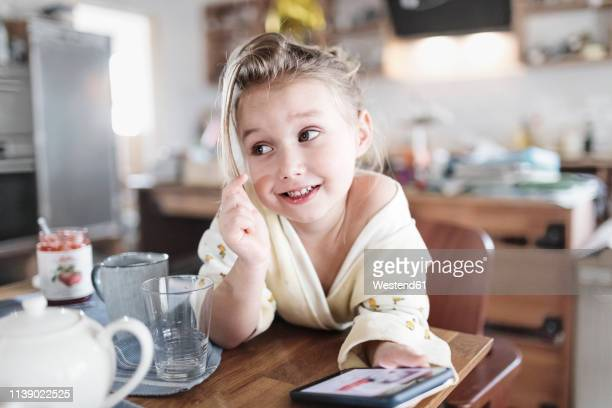 portrait of smiling little girl with smartphone in the kitchen - conspiracy stock pictures, royalty-free photos & images
